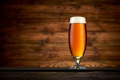 Glass of cold beer on wooden table background. Glass of cold beer on wooden background stock image