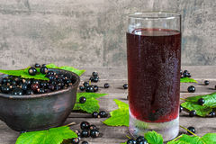 Glass of cold black currant juice with fresh berries in a bowl Royalty Free Stock Image