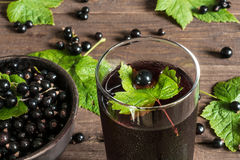 Glass of cold black currant juice on wooden table with ripe berr. Ies in pottery bowl and green leaves around. high angle Royalty Free Stock Photography