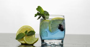 Glass with cold blue drink with leaves of mint, lime, lemon, black currants royalty free stock photo