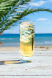 Glass of cold cidre or lemonade with ice on a seaside Stock Image