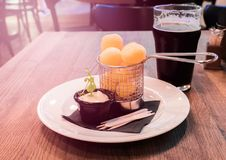 Glass of cold craft stout beer on the old table. In old fashioned pub with cheese snacks stock photo