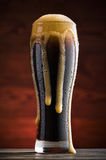 Glass of cold dark beer on the table Royalty Free Stock Images