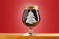 Glass of cold frothy dark beer on an old wooden table Stock Image