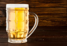 Glass of cold frothy lager beer on old wooden table Royalty Free Stock Photo