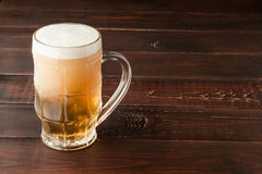 Glass of cold frothy lager beer on old wooden table Stock Photo