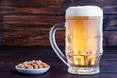 Glass of cold frothy lager beer and peanuts plate on wooden tabl Stock Images