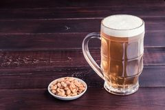 Glass of cold frothy lager beer and peanuts plate on wooden tabl Stock Photos