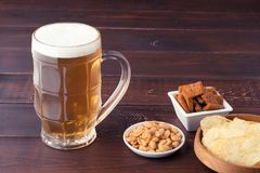 Glass of cold frothy lager beer and peanuts plate on wooden tabl. Glass of cold frothy lager beer and peanuts plate on an old wooden table Royalty Free Stock Photography