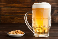 Glass of cold frothy lager beer and peanuts plate on wooden tabl. Glass of cold frothy lager beer and peanuts plate on an old wooden table Stock Images