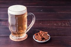 Glass of cold frothy lager beer and plate of snacks on wooden ta. Glass of cold frothy lager beer and plate of snacks on an old wooden table Royalty Free Stock Photo