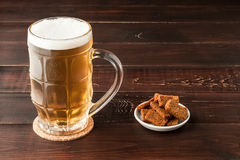 Glass of cold frothy lager beer and plate of snacks on wooden ta. Glass of cold frothy lager beer and plate of snacks on an old wooden table Royalty Free Stock Images