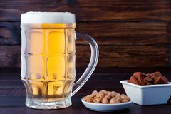 Glass of cold frothy lager beer and plate of snacks on wooden ta. Glass of cold frothy lager beer and plate of snacks on an old wooden table Stock Images