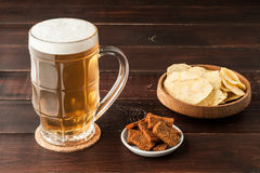 Glass of cold frothy lager beer and potato chips plate on wooden Royalty Free Stock Photo
