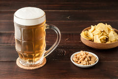 Glass of cold frothy lager beer and potato chips plate on wooden Royalty Free Stock Image