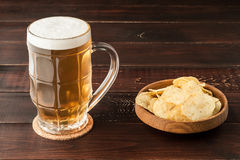 Glass of cold frothy lager beer and potato chips plate on wooden Stock Photography