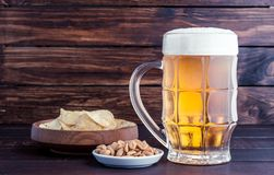 Glass of cold frothy lager beer and snacks on wooden table. Glass of cold frothy lager beer and snacks plate on an old wooden table Stock Image