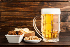 Glass of cold frothy lager beer and snacks on wooden table. Glass of cold frothy lager beer and snacks plate on an old wooden table Stock Images