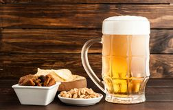 Glass of cold frothy lager beer and snacks on wooden table. Glass of cold frothy lager beer and snacks plate on an old wooden table Stock Photography