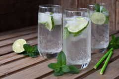 Glass of cold homemade lemonade or mojito cocktail with lime and mint on wooden background. Soda drink. Copy space. Stock Photos