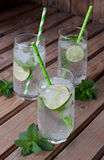 Glass of cold homemade lemonade or mojito cocktail with lime and mint on wooden background. Soda drink. Copy space. Stock Images