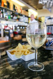 Glass of cold house white wine, Italy, Riccione. A glass of white house wine and chips on the counter of one of the bars on the riccone coast Stock Photo