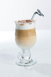 Glass of cold latte coffee topic cocolate cream on white background with desserts Royalty Free Stock Images