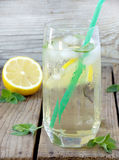 Glass of cold lemonade with ice, lemon, mint leaves and straw. Stock Image