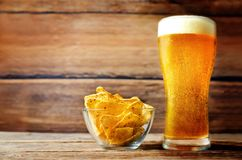 Glass of cold light beer with corn chips Royalty Free Stock Photography