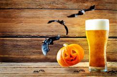 Glass of cold light beer with flying bats and pumpkin Stock Photos