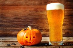 Glass of cold light beer with pumpkin on a wood background for H Stock Photos