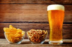 Glass of cold light beer with snacks on a wood background Stock Photo