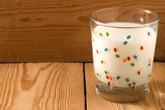 A glass of cold milk stands. On a wooden background Stock Photography