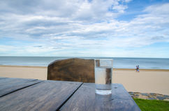 Glass of cold mineral water on the table of the beach background Stock Images