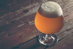 Unfiltered pale beer. Glass of cold pale unfiltered beer on a rustic wooden pub table Royalty Free Stock Image