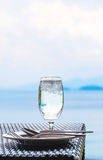 Glass of cold water on dining table with blue ocean background Stock Images