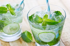 Glass of cold water with fresh mint leaves and cucumber with ice cubes on wooden background Royalty Free Stock Photography