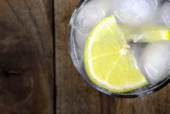 glass of cold water with ice and lemon on a wooden table. close up. royalty free stock images