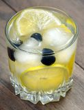 Glass of cold water with ice and lemon on a wooden table. Close up stock photos