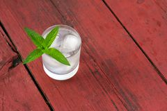 Glass of cold water with ice and mint on wooden table Stock Photography