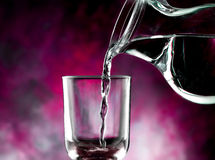 Glass of cold water. Jug of water poured into the glass Stock Images