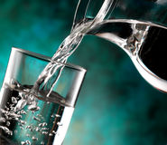 Glass of cold water. Jug of water poured into the glass Royalty Free Stock Photography