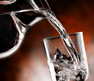 Glass of cold water. Jug of water poured into the glass Royalty Free Stock Images