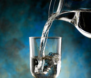 Glass of cold water. Jug of water poured into the glass Royalty Free Stock Photos
