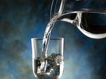 Glass of cold water. Jug of water poured into the glass Stock Photography