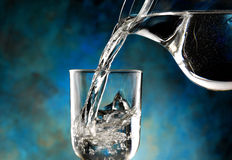 Glass of cold water. Jug of water poured into the glass Stock Image