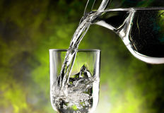 Glass of cold water. Jug of water poured into the glass Stock Photos