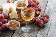 Glass of cold white wine and snacks on a wooden background Royalty Free Stock Image