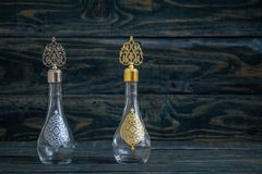 Glass Cologne Bottle with Ottoman Pattern and Metal Lid. On blue background royalty free stock photos
