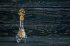 Glass Cologne Bottle with Ottoman Pattern and Metal Lid. On blue background royalty free stock photo